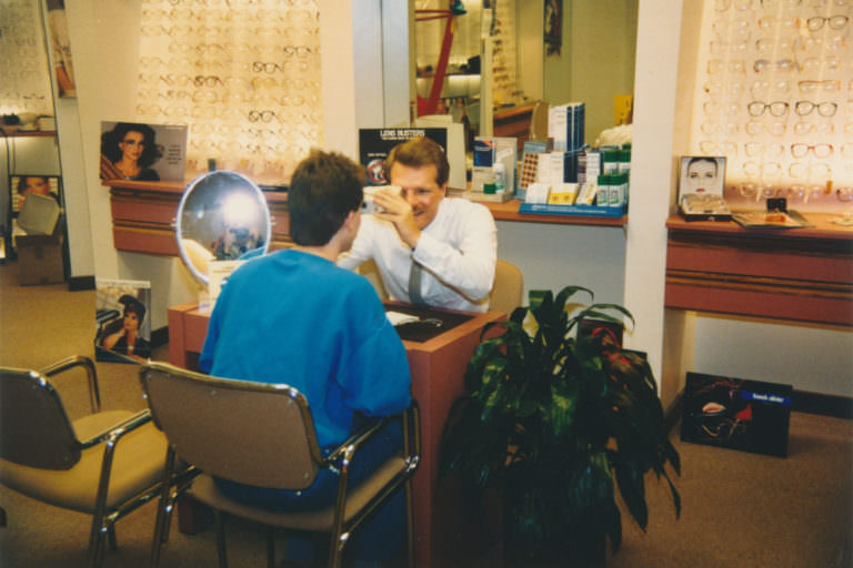 Optician Daniel Klein serving a client at his optical store in the mid to late 1980s.