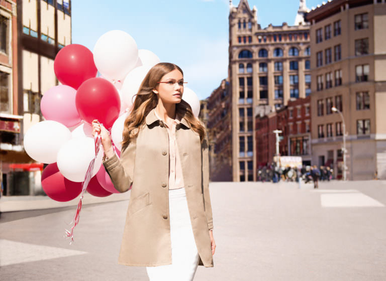 Woman in Silhouette frames holding balloons in a European city.