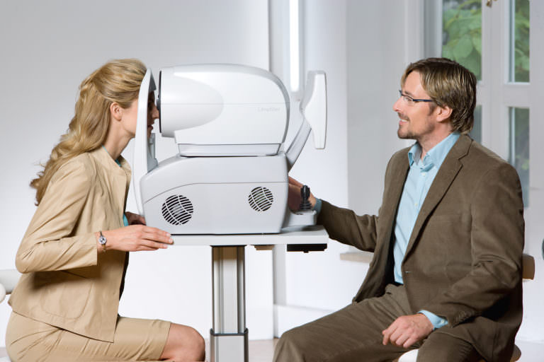 An optometrist uses the Zeiss i.Scription plus auotrefracter to test a patient's eyes.