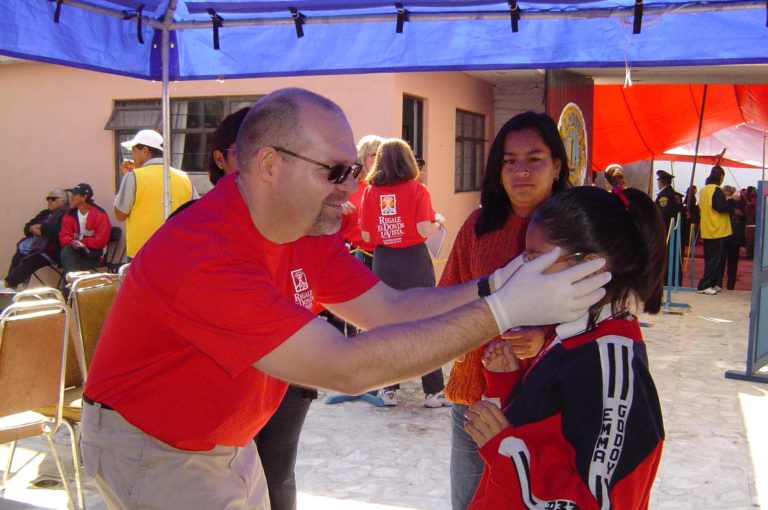 Klein Optical optician Daniel Klein fits a child with donated glasses during a mission in Mexico.
