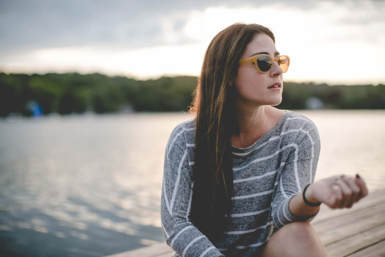 Woman wearing Klein 1991 sunglasses out on a lake.