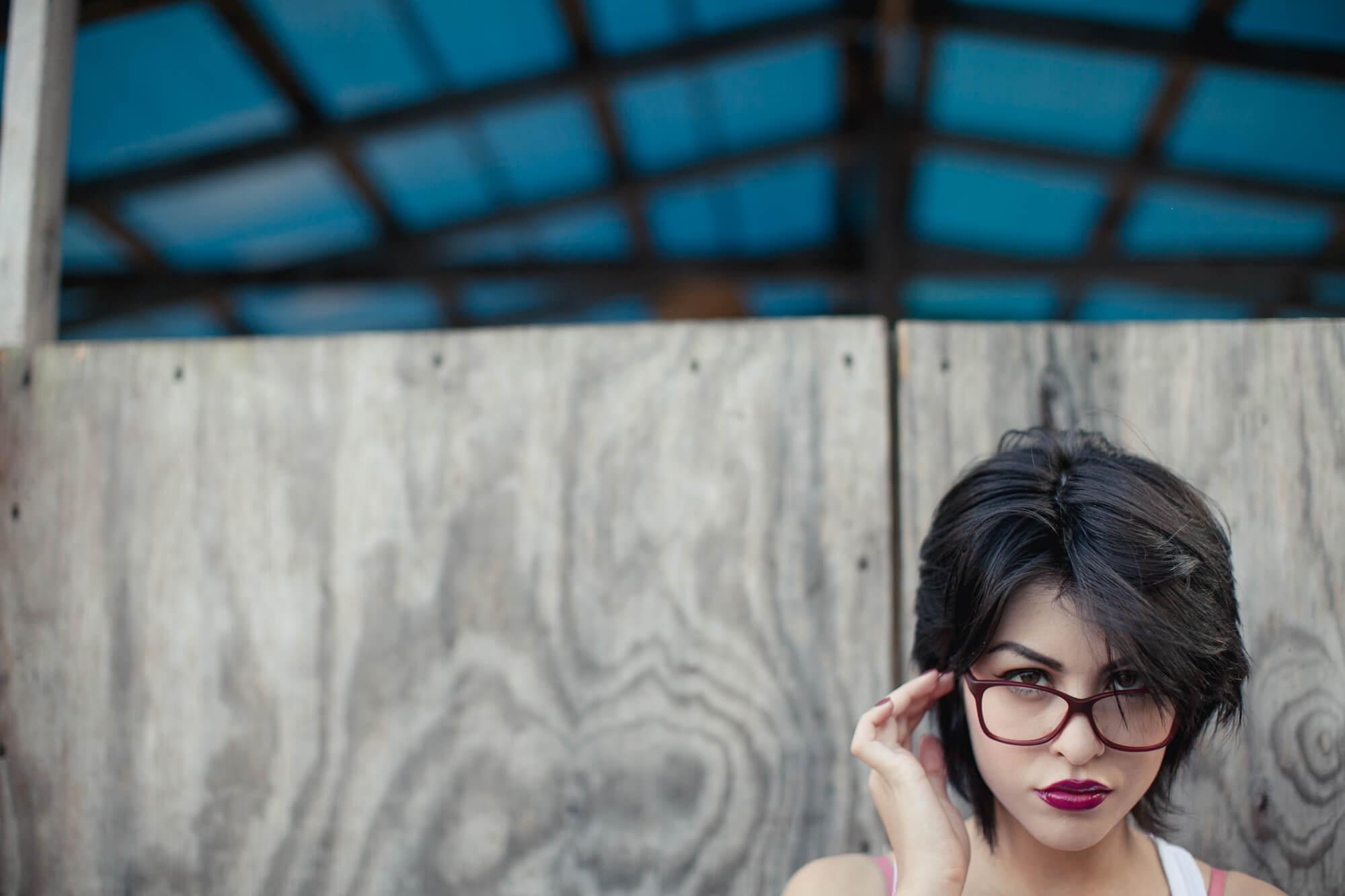 Woman wearing Klein 1991 Gina plastic eyeglass frames in tortoise/red.