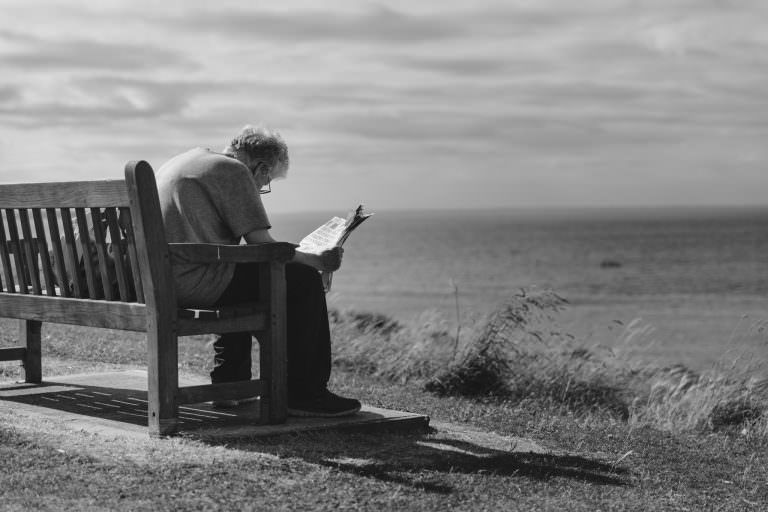 Man outdoors on bench near coast struggling to read a newspaper.