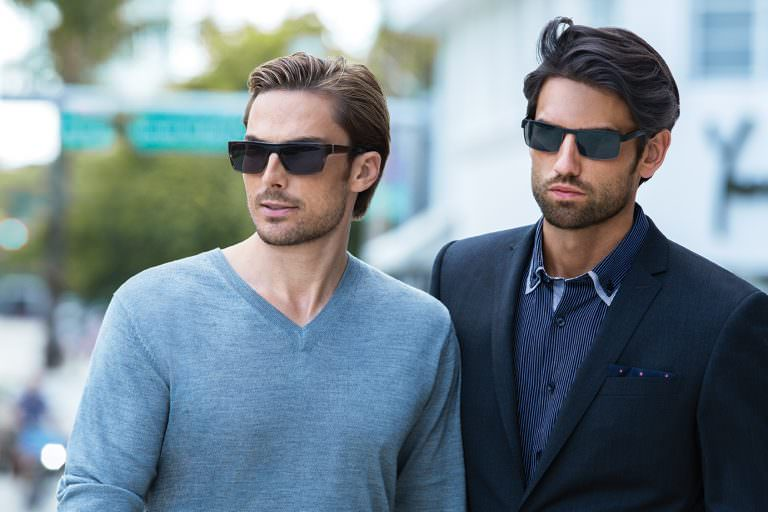 Man wearing EVATIK E-1045 plastic sunglasses in grey next to man wearing EVATIK E-1042 metal sunglasses in black.