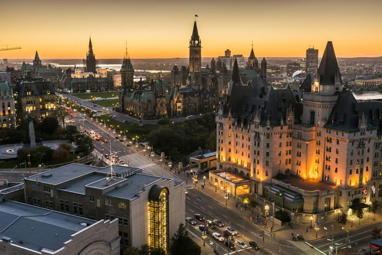 Aerial view of downtown Ottawa at dusk, with the Parliament Buildings highlighted in the background.