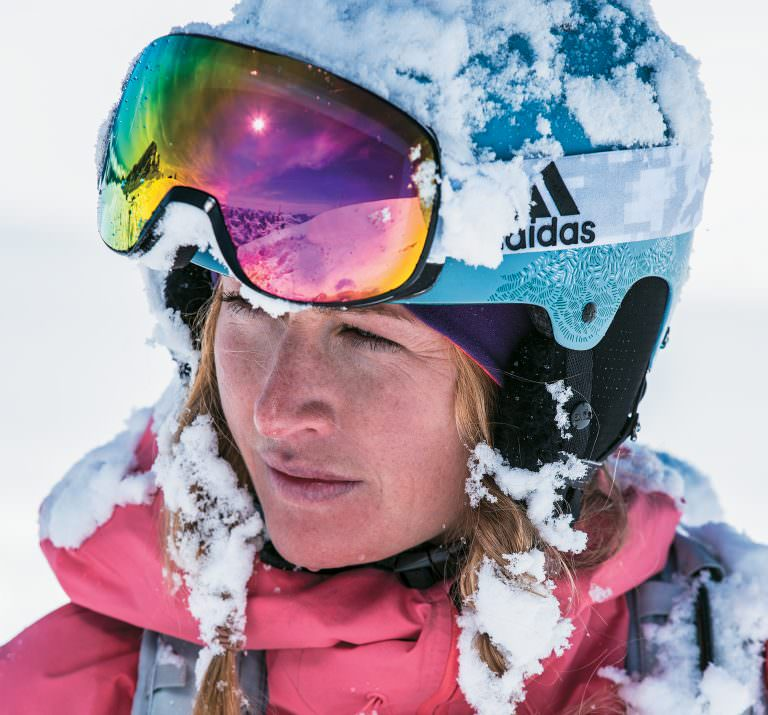 Woman skiing wearing adidas Sport Eyewear Progressor C ski goggles in shiny black/white with purple mirror lens.