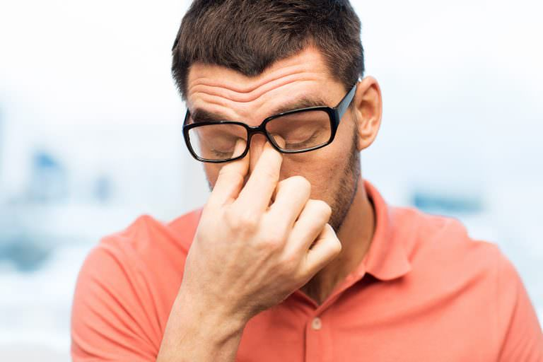 A man rubs his eyes while suffering from visual stress.