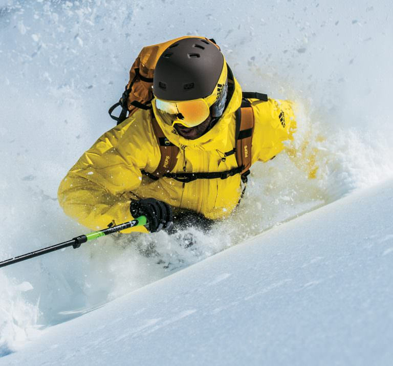 Man skiing wearing adidas Sport Eyewear Progressor S ski goggles in shiny bright yellow with gold mirror lens.
