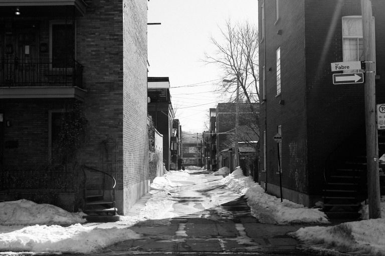 A desolate street with snow piles in an older urban neighbourhood.