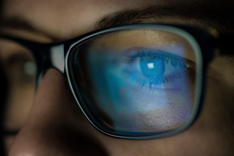 A woman experiences reduced glare with anti-reflective lenses by ZEISS while looking at a digital screen.