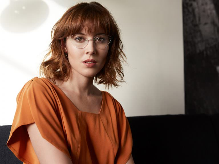 Paula Goldstein wearing Silhouette Titan Minimal Art PULSE 4547 rimless titanium eyeglasses in melon/grey.