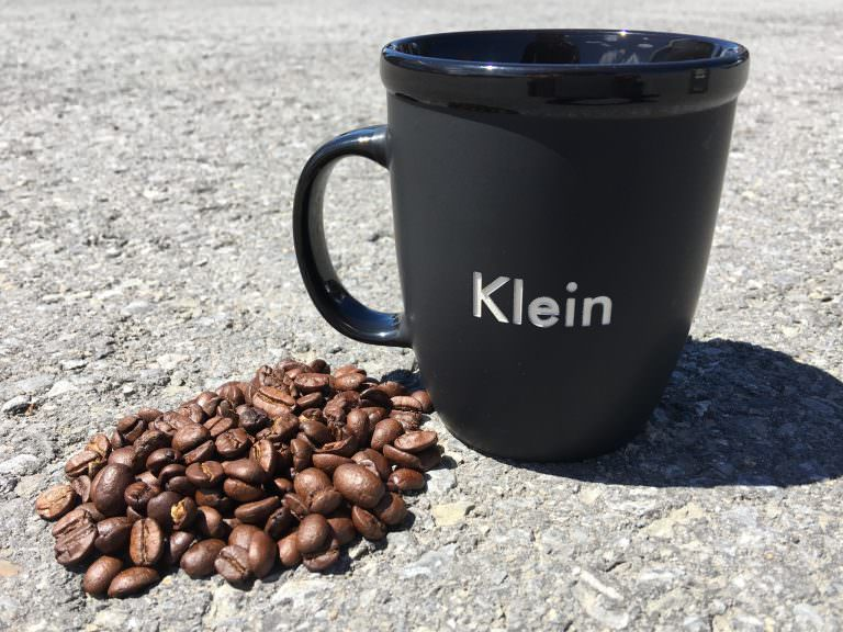 A pile of whole coffee beans next to a Klein 12 oz Ceramic Bistro Mug on asphalt.