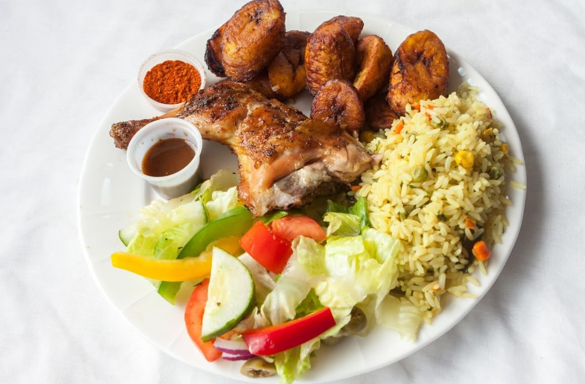 Signature Charcoal Grilled Chicken Platter by Pili Pili Grilled Chicken including seasoned rice, plantain, and garden salad.